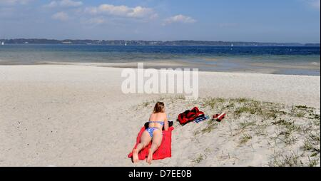 A young woman enjoys the sun at the Solituede beach at the fjord near Flensburg, Germany, 06 May 2013. Weather is - Stock Photo