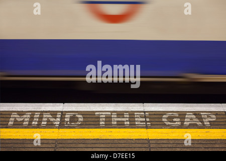 Bank underground station 'Mind the Gap' sign painted on the station platform with fast moving tube train in the - Stock Photo