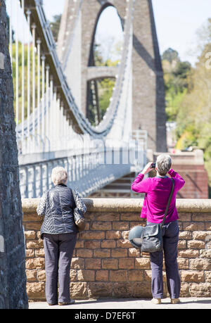 Bristol, UK. 6th May 2013. Two women stop to take a photograph of Brunel's suspension bridge in Clifton, Bristol - Stock Photo