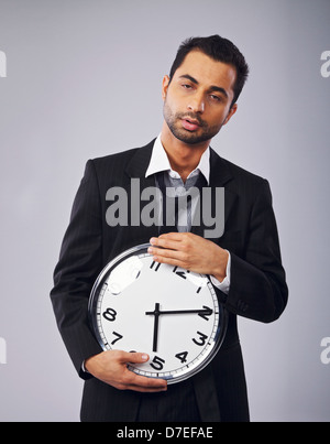 Sleepy office worker holding a clock - Stock Photo