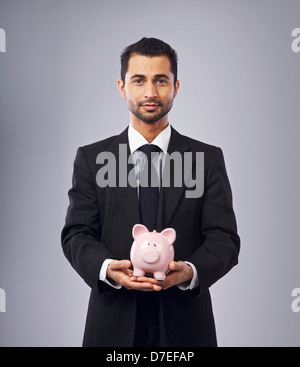 Corporate man holding a coin bank - Stock Photo