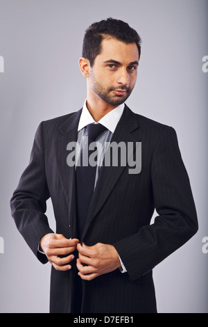 Young manager looking at you while buttoning his suit - Stock Photo