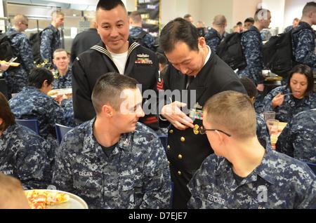 Recruits look at a Japan Maritime Self-Defense Force uniform - Stock Photo