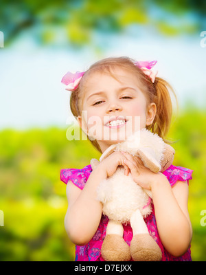 Sweet little girl hug soft toy outdoors in spring time, playing game on backyard, day care, happy childhood concept - Stock Photo