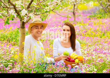 Happy smiling couple on picnic in beautiful blooming garden, eating tasty fresh fruits, enjoying spring nature - Stock Photo