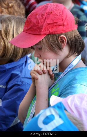 Boy praying at the childrens Last Supper at 34th German Evangelical Church Congress in Hamburg, Germany - Stock Photo