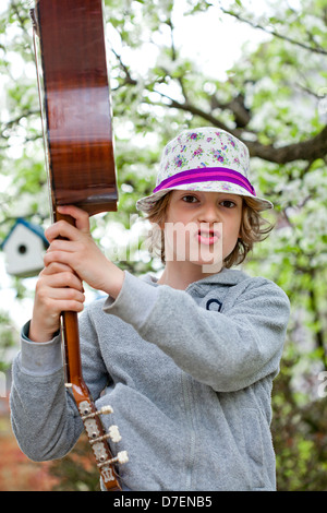 Portrait of a boy playing an acoustic guitar outdoor in the garden. - Stock Photo