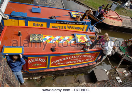Visitors exploring boats in a waterways museum at Ellesmere Port on Merseyside. - Stock Photo