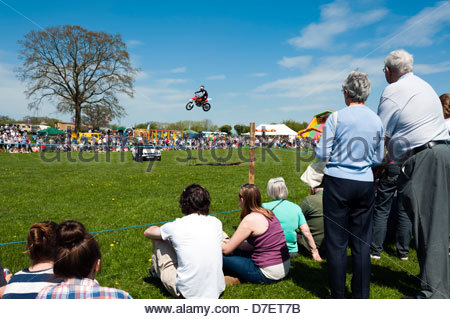 Flying Ryan motorcycle stunt man leaping a car at Dilwyn village show, Herefordshire, UK. - Stock Photo