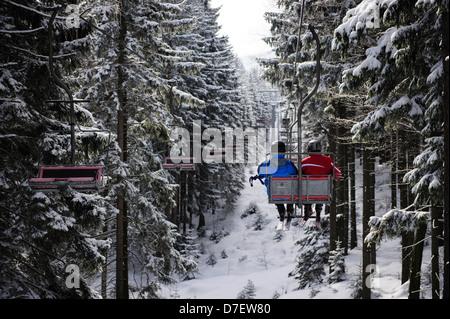 Two skiers on a chair lift, Szklarska Poreba, Poland. - Stock Photo