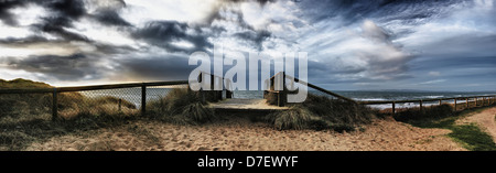 Panoramic view of a boardwalk and fence on a beach at hengistbury head;Dorset england - Stock Photo