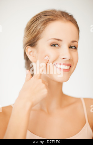 woman pointing at her cheek - Stock Photo
