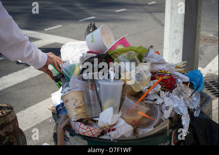 A passerby disposes of a beverage can at an overflowing trash basket in Chelsea in New York - Stock Photo
