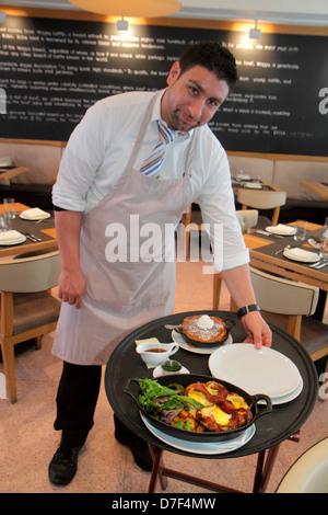 Miami Beach Florida Ocean Drive Betsy Ross Hotel BLT Steak restaurant Hispanic man waiter job food tray serving - Stock Photo