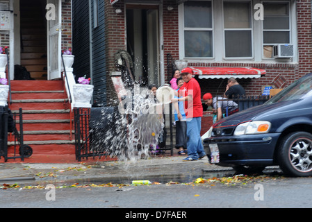 BROOKLYN, NY - OCTOBER 30: People pumping water out of building basement at the Brighton Beach neighborhood - Stock Photo