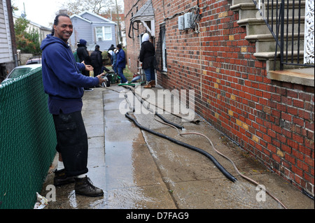 BROOKLYN, NY - OCTOBER 30: People pumping water out of building basement in the Sheepsheadbay neighborhood - Stock Photo