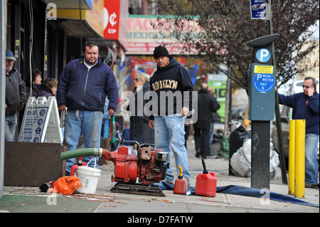 BROOKLYN, NY - NOVEMBER 01: People pumping water out buildings at the Brighton Beach neighborhood - Stock Photo