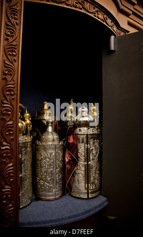 An open cabinet with several Torah (old testament) scrolls closed in gold and silver fancy containers. - Stock Photo