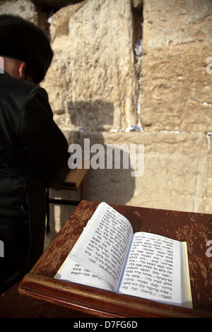 The biblical Book Psalms opened on one pages morning prayer resting on pedistal . There's also Jewish orthodox man - Stock Photo