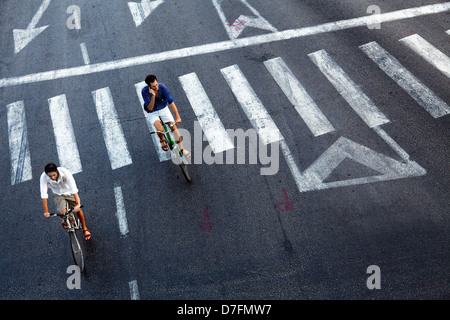Tel-Aviv Israel - October 8th 2011: High angle view two adult men riding on bicycles at empty Maariv intersection - Stock Photo