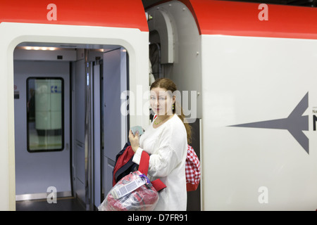 Young woman with bags boarding in Narita express to Tokyo station from airport, Japan - Stock Photo