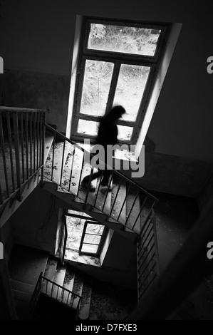 Woman running down stairs - Stock Photo