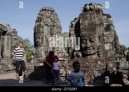Tourists pass one of the over 200 enigmatic faces carved into the towers of the Bayon, the temple in the centre - Stock Photo