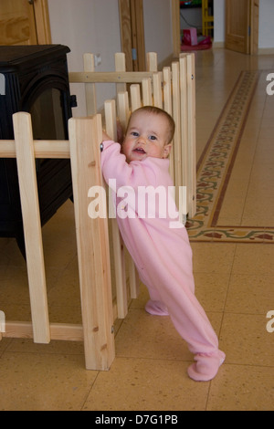 one year old baby girl who can barely stand by herself - Stock Photo