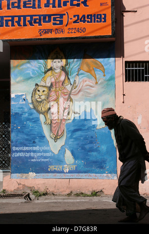 A local man walks past a mural of India in the bazaar in Uttarkashi. - Stock Photo