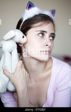 Head shoulders portrait young adult Caucasian woman in her early 20's wearing bunny ears holding funky sheep doll - Stock Photo