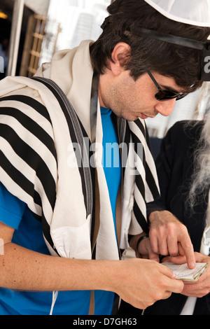 An adult Caucasian Jewish man wearing praying shawl Yarmulke Phylacteries while being helped by Rabbi praying. This - Stock Photo