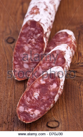 slices of fuet on rustic wood - Stock Photo