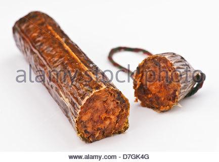 Cut Iberian sausage bar on white base - Stock Photo