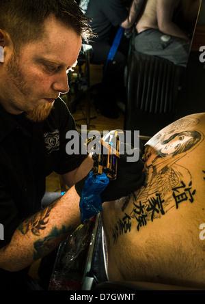 Award winning tattooist Dualta 'Duke' Kellegher at work - Stock Photo