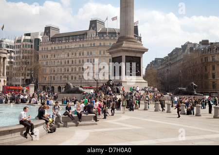 People sitting around the fountains on a sunny day, Trafalgar Square, Central London WC2, UK - Stock Photo