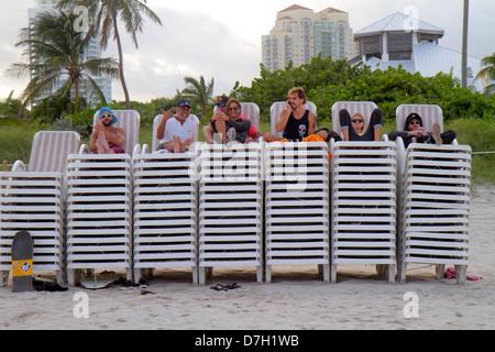 Miami Beach Florida Atlantic Ocean Hispanic man woman couple sitting stacked lounge chairs rental - Stock Photo