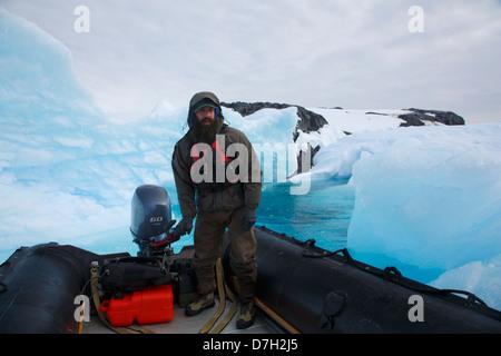 Zodiac Crusing through icebergs, Detaille Island, South of the Antarctic Circle, Antarctica. - Stock Photo