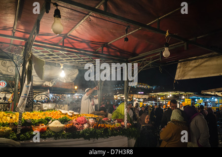 Morocco, Marrakesh - the Night Market and food stalls in Jamaa el Fna after dark. Seafood chef's display. - Stock Photo