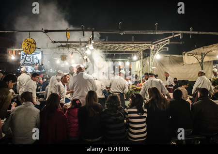 Morocco, Marrakesh - the Night Market and food stalls in Jamaa el Fna after dark. Busy chefs at work. - Stock Photo