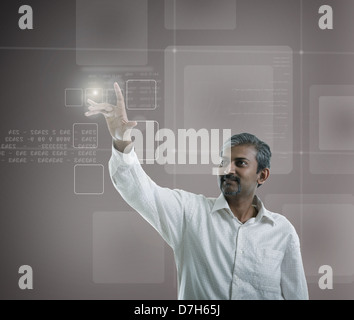 asian indian businessman pressing high tech type of modern buttons on a virtual background - Stock Photo