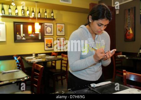 Miami Florida Coral Way 1401 Argentinean Bistro restaurant Hispanic teen girl waitress working job writing taking - Stock Photo