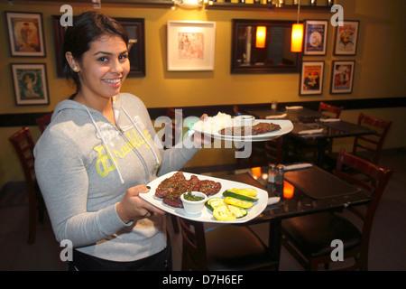 Miami Florida Coral Way 1401 Argentinean Bistro restaurant Hispanic teen girl waitress working job serving plates - Stock Photo