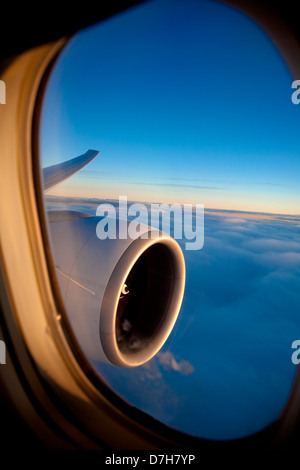Passenger view through the window of a jet plane showing sky, clouds, jet engine and wing. - Stock Photo