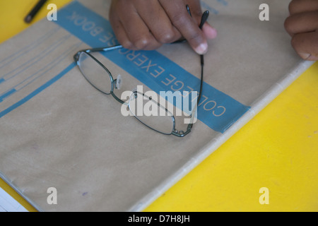 close up on a pair of glasses on top of a school book - Stock Photo