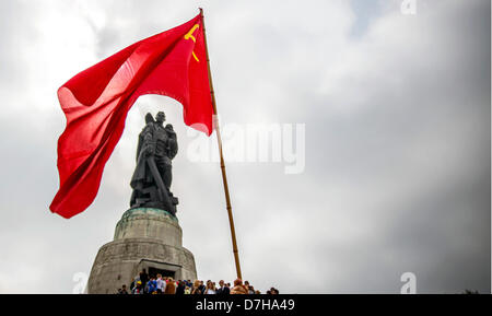 A red Soviet flag waves at the Soviet War Memorial while visitors are lining up to lay flowers and wreaths to commemorate - Stock Photo