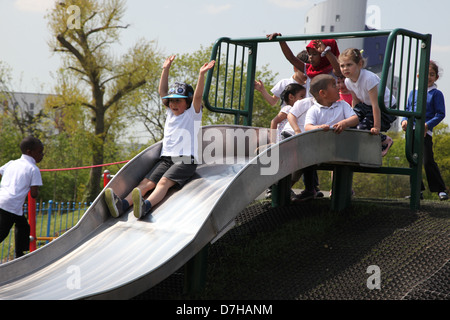 Children playing on a slide in a playground in London - Stock Photo