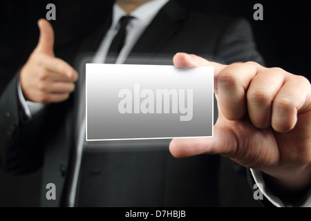 Businessman in black suit and a white shirt with a black tie, shows business card with copy space - Stock Photo