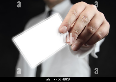 Businessman in white shirt with a black tie, shows business card with copy space - Stock Photo