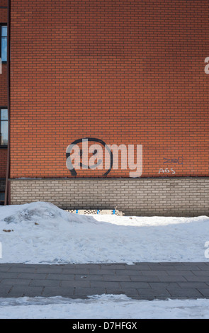 A smiley face painted on a block of flats in the suburbs of snow covered Vilnius. - Stock Photo