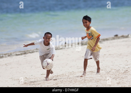 Young local boys playing football on a beach in Boracay, Philippines - Stock Photo